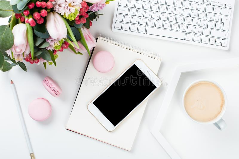 Het werkbureau van damebloggers met roze bloemen en macaron cakes op w royalty-vrije stock foto's