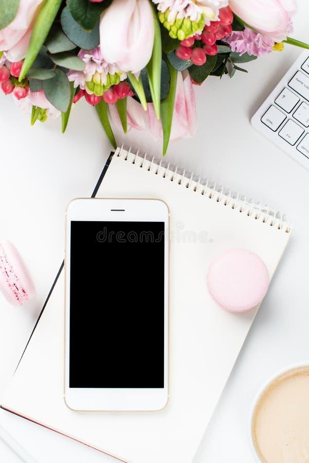 Het werkbureau van damebloggers met roze bloemen en macaron cakes op w stock afbeeldingen