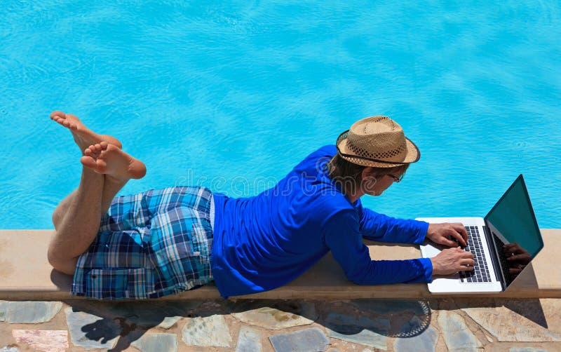 Het werken aan laptop bij de pool royalty-vrije stock afbeelding