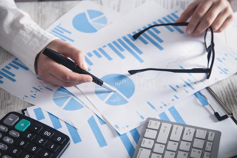 Het werken in bureau Financi?le grafieken en Investering stock foto's