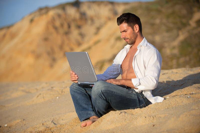 Het werken in laptop bij het strand royalty-vrije stock afbeelding