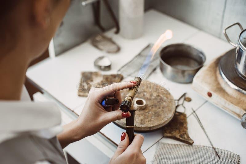 Het werken met een brand De handen die van de vrouwelijke juwelier en zilveren ring solderen lassen bij haar juwelen die workshop royalty-vrije stock foto's