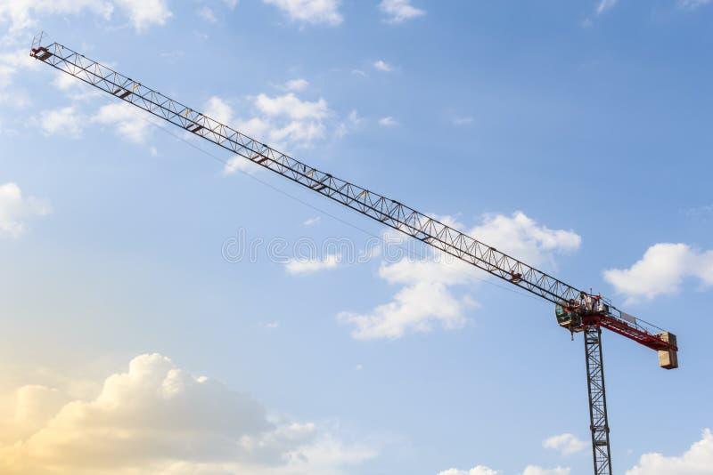 Het werken met een kraan De toren van de bouwkraan op blauwe hemelachtergrond Lege ruimte voor tekst De idylle van de zomer Het c royalty-vrije stock afbeelding