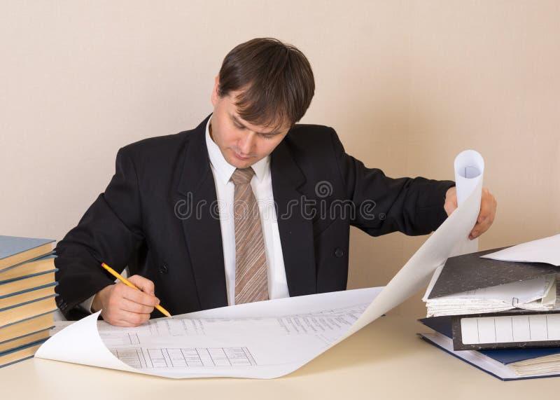 Het werken met tekening bij de lijst in bureau stock foto's