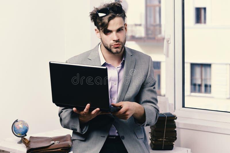 Het werken online en gadgetsconcept De koele kerel zit op lijst en de werken Mens of manager met binnen varkenshaar en ernstig ge royalty-vrije stock afbeelding