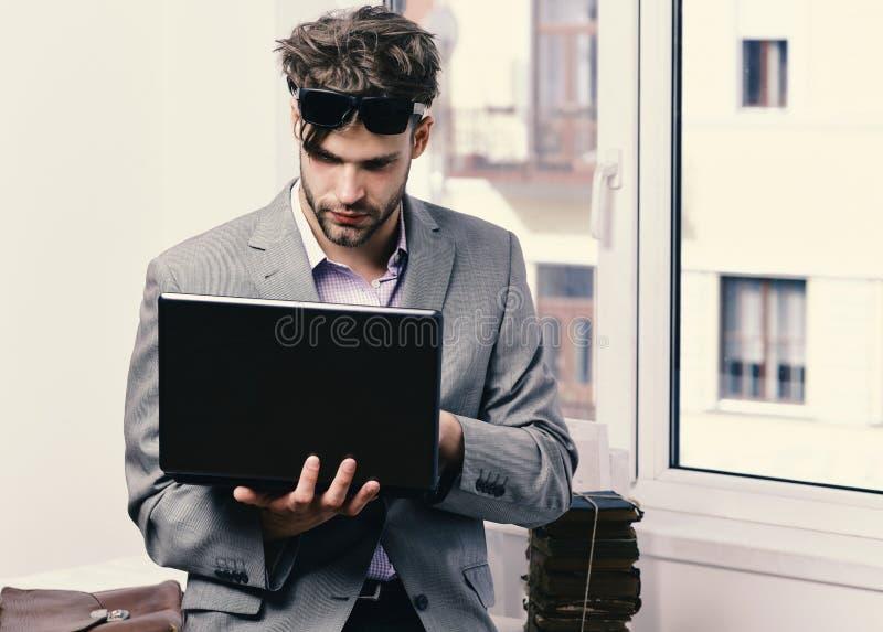 Het werken online en gadgetsconcept Mens of manager met varkenshaar en ernstig gezicht in zonnebril royalty-vrije stock foto