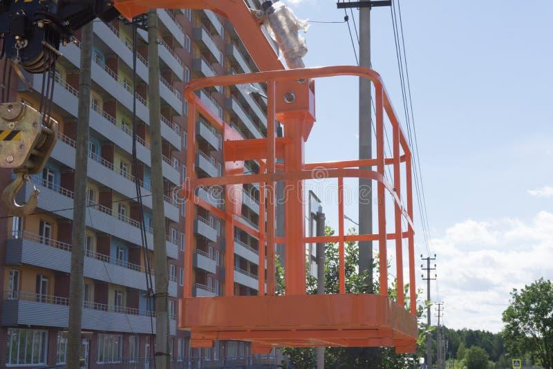 Het werkende platform van de kraan` s wieg, kersenplukker of mand in de bouwwerf stock afbeelding