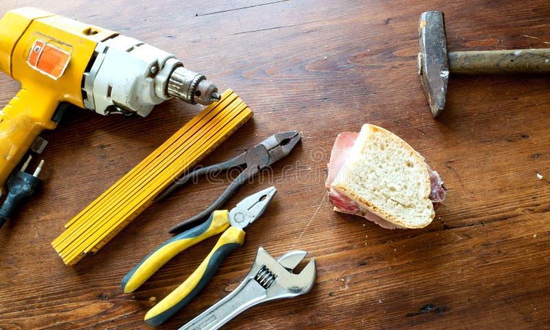 Het werkhulpmiddelen en sandwich met Italiaanse worst stock afbeelding