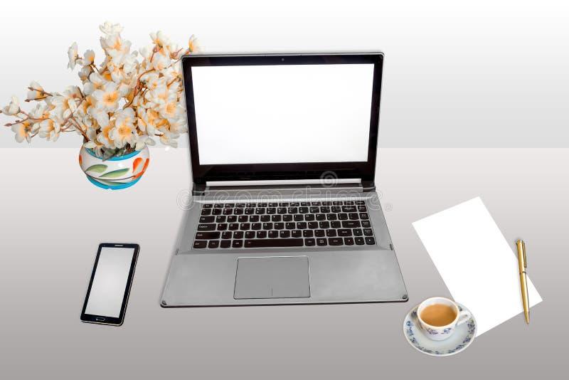 Het werkplaats met laptop slim telefoon wit leeg document en pen met geïsoleerde ochtendthee stock fotografie