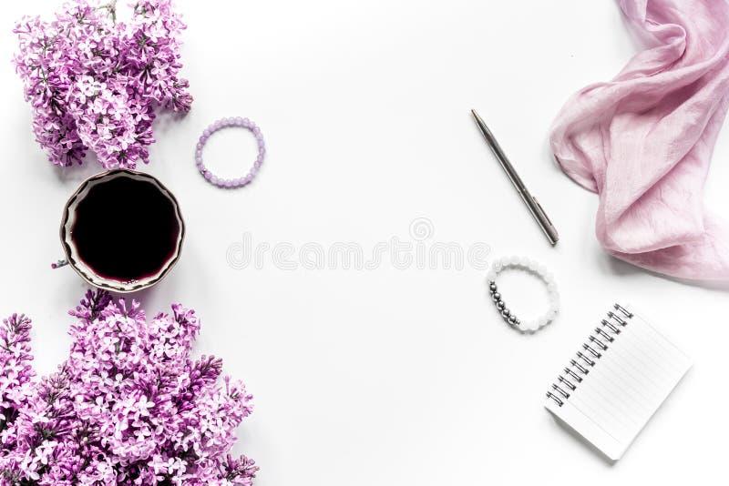 Het werkplaats met lilic bloemen en koffie voor vrouw op wit bureau achtergrond hoogste meningsmodel royalty-vrije stock fotografie