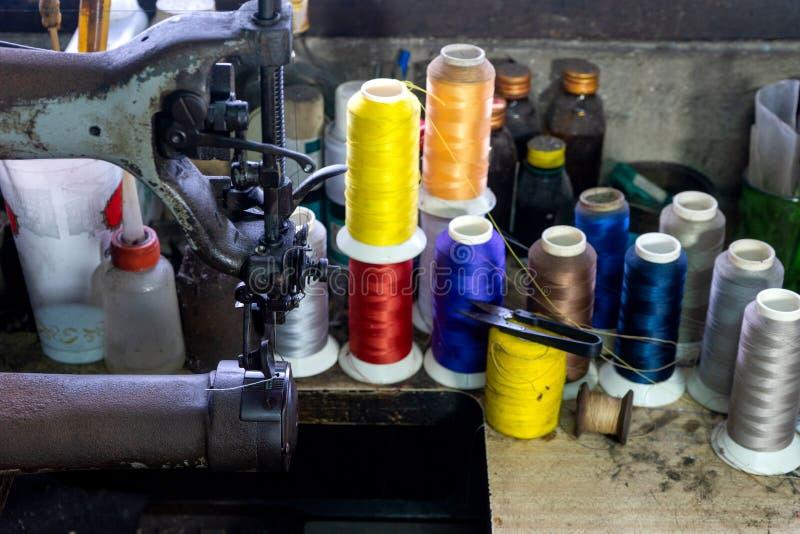 het werkplaats van de schoenmaker met het naaien van leer stock afbeeldingen