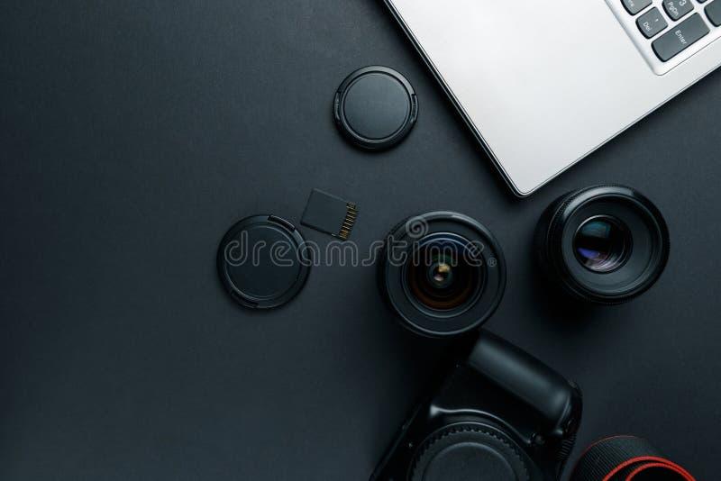 Het werkruimte op zwarte lijst van fotograaf Minimale werkruimte met Laptop, camera en lensexemplaarruimte op donkere achtergrond stock afbeelding