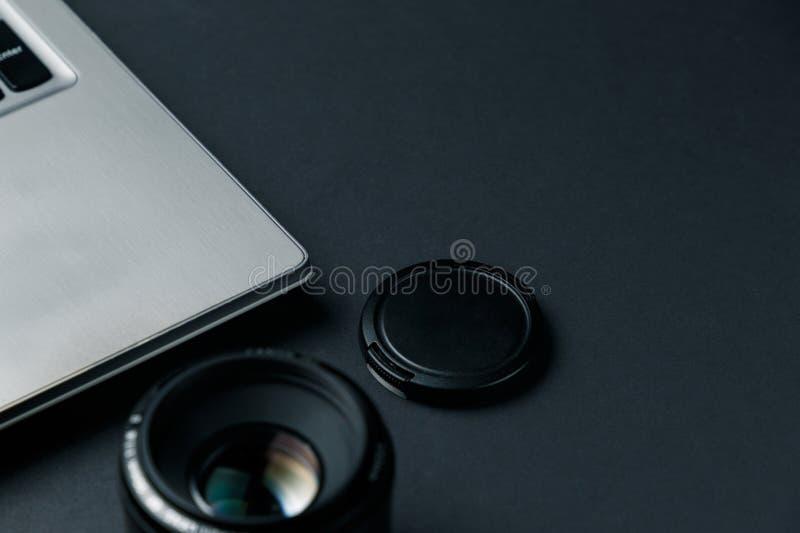 Het werkruimte op zwarte lijst van fotograaf Minimale werkruimte met Laptop, camera en lensexemplaarruimte op donkere achtergrond stock afbeeldingen