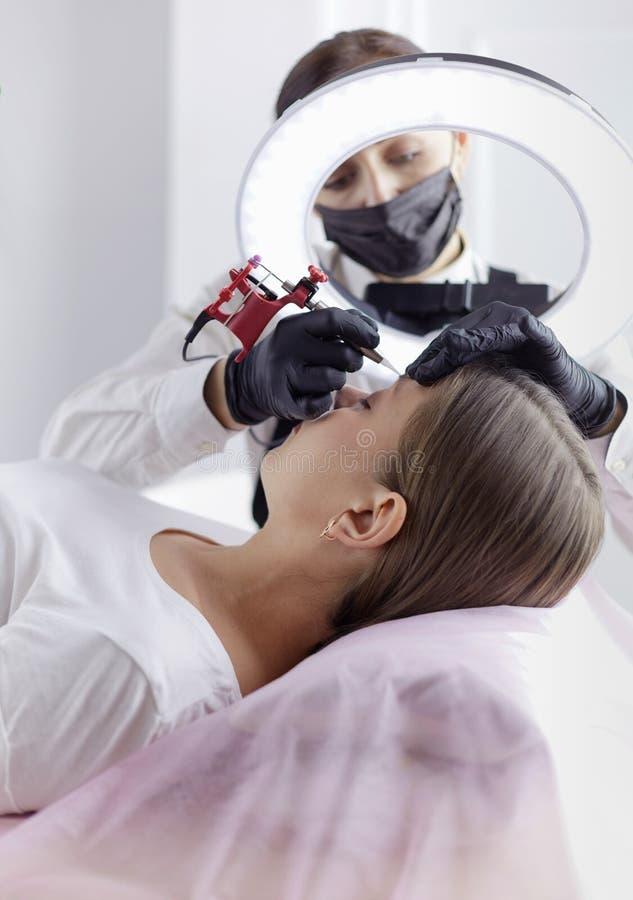 Het werkstroom van Microbladingswenkbrauwen in een schoonheidssalon Vrouw die haar oog hebben - brows gekleurd royalty-vrije stock foto