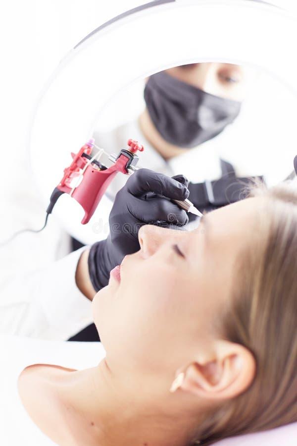 Het werkstroom van Microbladingswenkbrauwen in een schoonheidssalon Vrouw die haar oog hebben - brows gekleurd stock foto