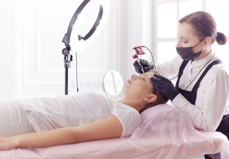 Het werkstroom van Microbladingswenkbrauwen in een schoonheidssalon Vrouw die haar oog hebben - brows gekleurd stock fotografie