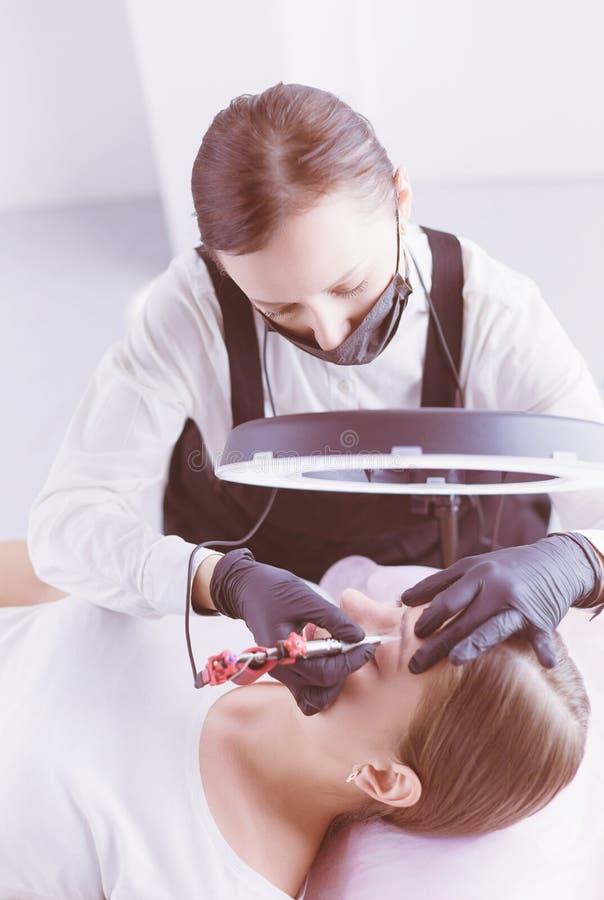 Het werkstroom van Microbladingswenkbrauwen in een schoonheidssalon Vrouw die haar oog hebben - brows gekleurd royalty-vrije stock fotografie