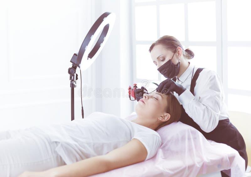 Het werkstroom van Microbladingswenkbrauwen in een schoonheidssalon Vrouw die haar oog hebben - brows gekleurd stock afbeeldingen