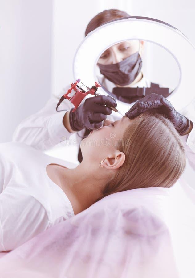 Het werkstroom van Microbladingswenkbrauwen in een schoonheidssalon Vrouw die haar oog hebben - brows gekleurd stock foto's