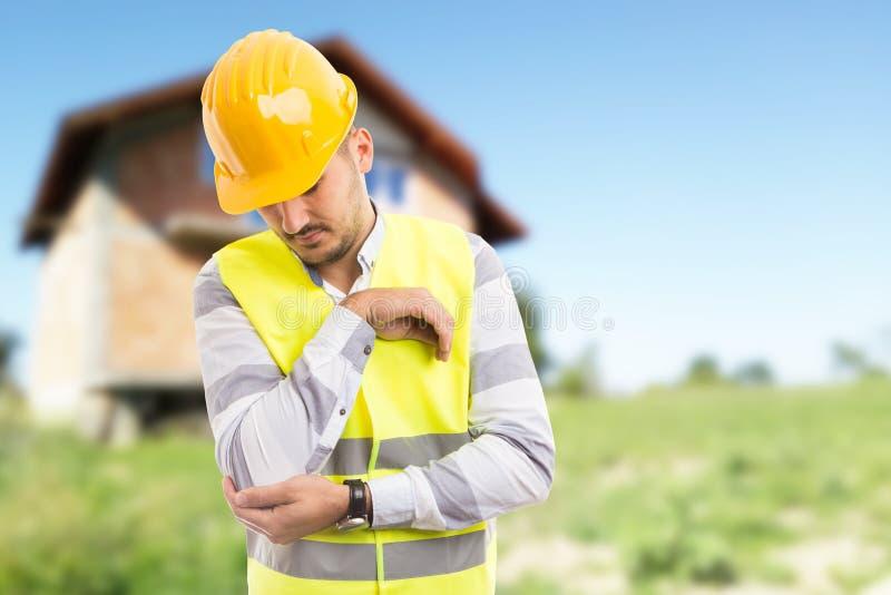 Het werkverwonding en pijnlijk elleboogconcept met bouwvakker stock afbeelding