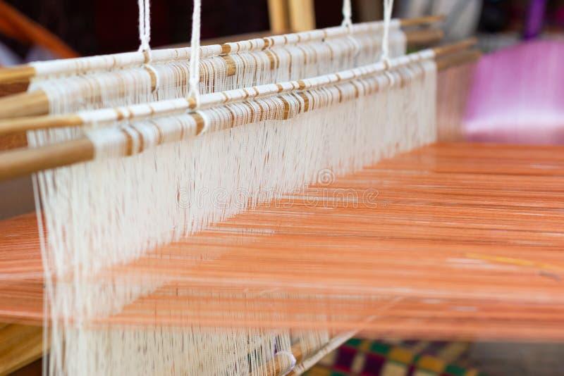 Het weven materiaalhuishouden het weven - Detail van wevend weefgetouw voor eigengemaakte zijde stock foto's