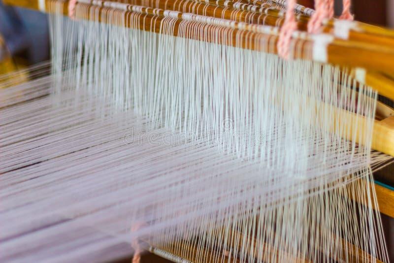 Het weven materiaalhuishouden het weven - Detail van wevend weefgetouw voor eigengemaakte zijde royalty-vrije stock foto