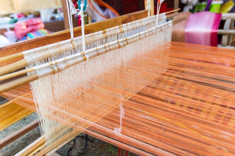 Het weven materiaalhuishouden het weven - Detail van wevend weefgetouw voor eigengemaakte zijde royalty-vrije stock fotografie