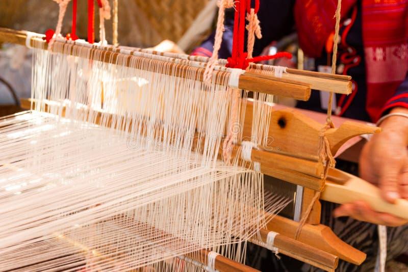 Het weven materiaalhuishouden het weven - Detail van wevend weefgetouw voor eigengemaakte zijde stock fotografie