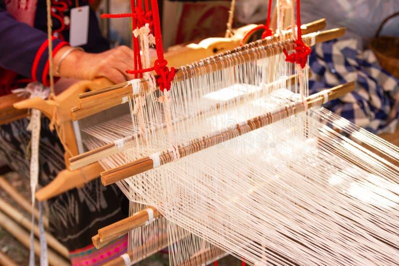 Het weven materiaalhuishouden het weven - Detail van wevend weefgetouw voor eigengemaakte zijde stock afbeeldingen