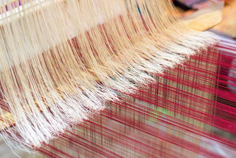 Het weven materiaalhuishouden het weven - Detail van wevend weefgetouw voor eigengemaakte zijde royalty-vrije stock foto's