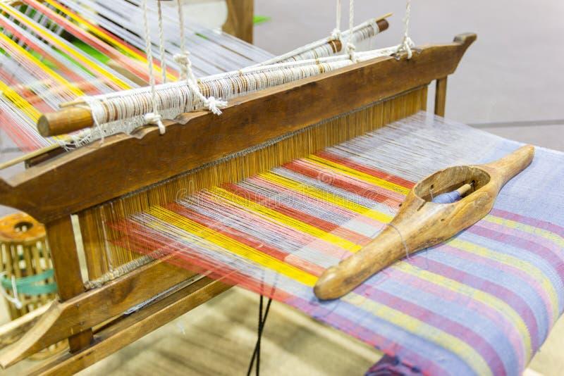 Het weven materiaalhuishouden het weven - Detail van wevend weefgetouw voor eigengemaakte zijde stock afbeelding