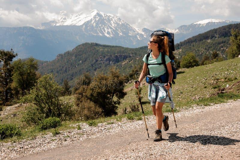 Het wijfje backpacker loopt onderaan de weg in heuvels royalty-vrije stock foto