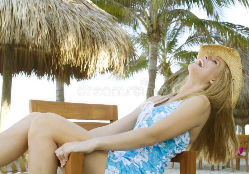 Het wijfje dat van de blonde terug in stoel het lachen leunt royalty-vrije stock foto's