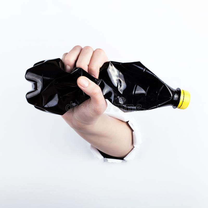 Het wijfje deelt van het gat in paperman uit, houdend een lege zwarte plastic fles Isoleer op witte achtergrond royalty-vrije stock fotografie
