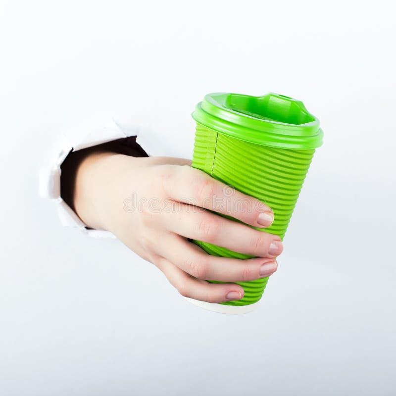 Het wijfje deelt van het gat in paperman uit, houdt een groen glas koffie met hem Isoleer op witte achtergrond royalty-vrije stock afbeelding