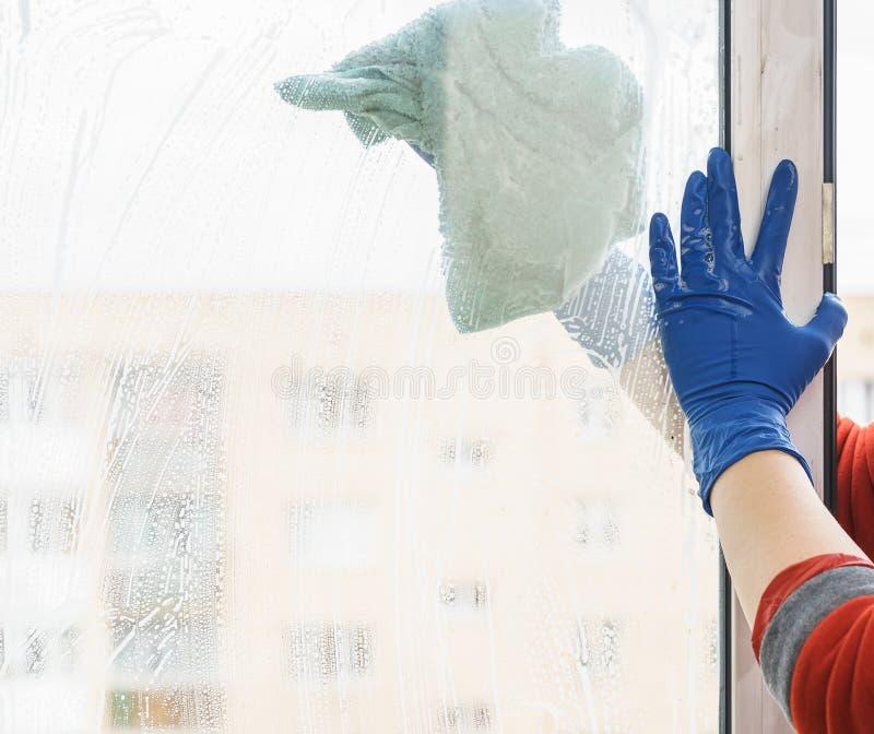 Het wijfje dient blauwe handschoenen in die venster schoonmaken royalty-vrije stock foto's