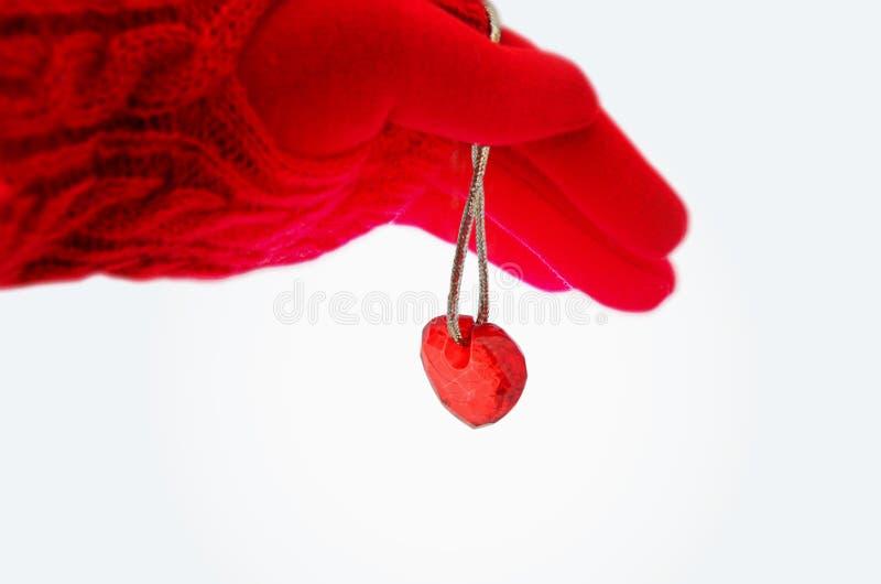 Het wijfje dient een rode handschoen en een rood die hart op een koord in op witte achtergrond wordt geïsoleerd beeld stock afbeeldingen
