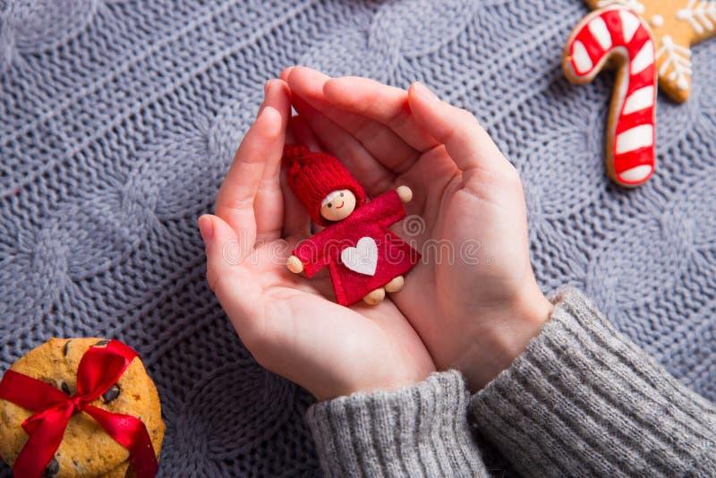 Het wijfje dient grijze gebreide sweater in houdend weinig pop op Chri stock afbeeldingen