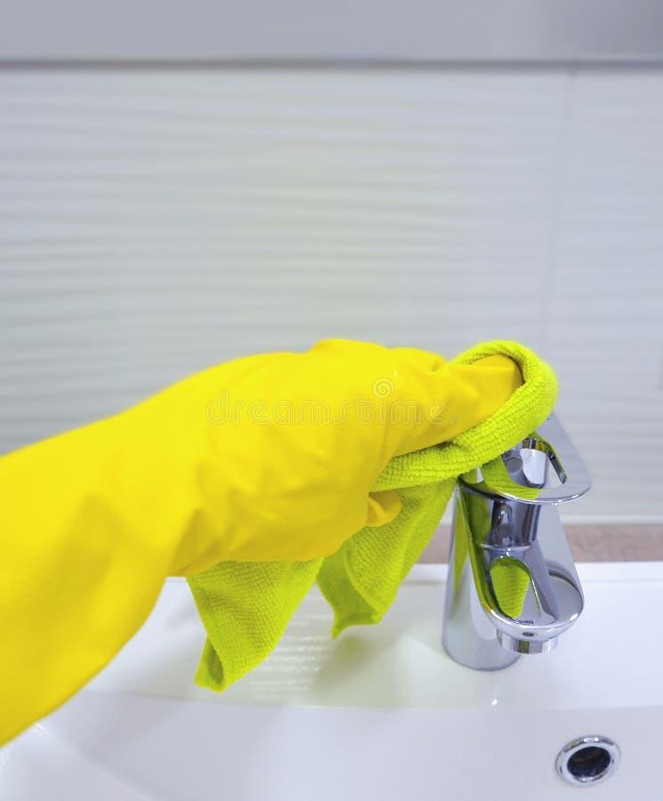 Het wijfje dient handschoen in afveegt een kraan in de badkamers beeld royalty-vrije stock afbeeldingen