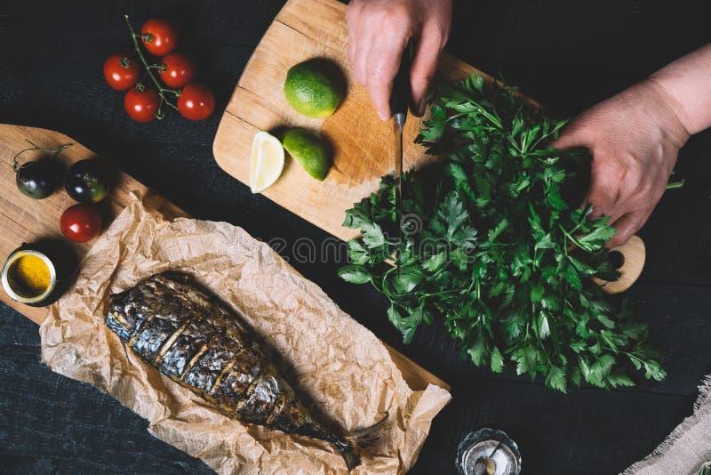Het wijfje dient kokende proces paprika op scherpe raad op een zwarte achtergrond van de oude houten raads uitstekende hoogste me stock afbeeldingen