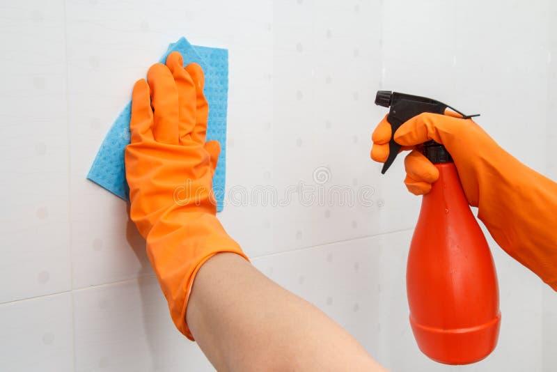 Het wijfje dient oranje rubberhandschoenen in houdt fles van detergent a stock foto