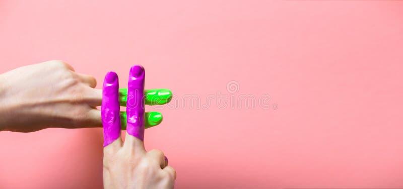 Het wijfje dient verf in in een hashtagteken wordt gekruist op een gekleurde achtergrond, creatieve reclame, sociaal netwerkencon stock foto's