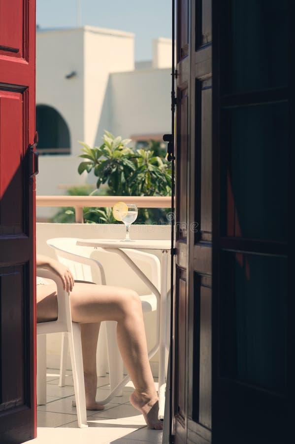 Het wijfje in een zwempak zit op het balkon van een oud Grieks gebouw met citroenwater in een glas Vrouwelijke benen op het balko royalty-vrije stock afbeelding