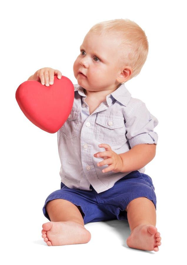 Het wijfje en overhandigt weinig jongenszitting die rood hart geïsoleerd houden stock afbeelding