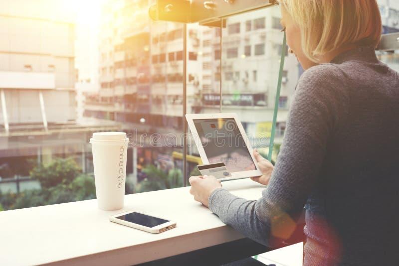 Het wijfje gebruikt creditcard voor het winkelen in Internet-opslag via digitale tablet stock fotografie