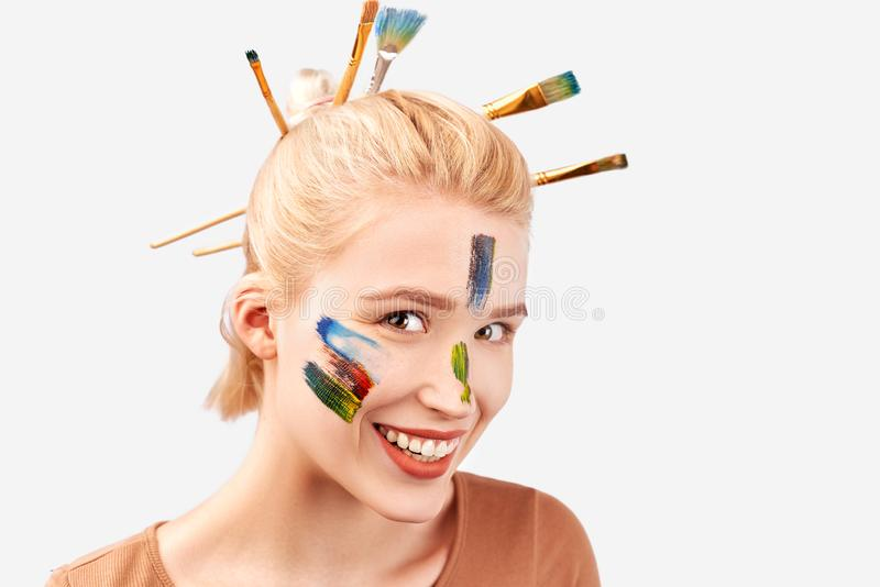 Het wijfje heeft artistieke make-up in de vorm van slagen acrylverf Modieus Loodjeskapsel met geplakte borstels in blond haar stock fotografie