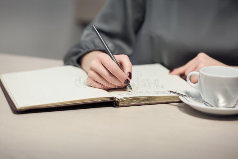 Het wijfje heeft koffiepauze en het schrijven nota's in agenda of blocnote; stock foto