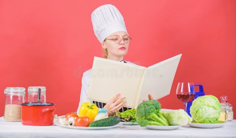 Het wijfje in hoed en schort kent alles over culinaire arts. Culinaire deskundige Vrouwenchef-kok die gezond voedsel koken Meisje royalty-vrije stock afbeeldingen