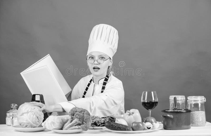 Het wijfje in hoed en schort kent alles over culinaire arts. Culinaire deskundige Vrouwenchef-kok die gezond voedsel koken Meisje royalty-vrije stock fotografie