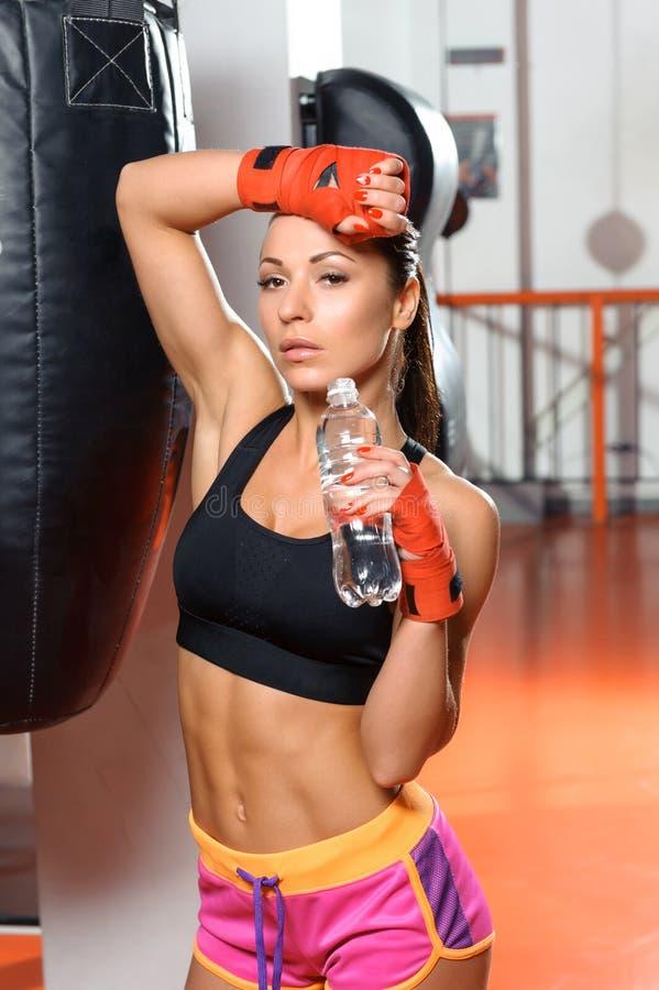 Het wijfje kickboxer drinkt water stock afbeelding